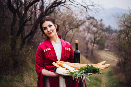 Photo for Young beautiful girl wearing traditional georgian dress holds a tray full of traditional georgian food: cheese, bread, greens and wine. - Royalty Free Image