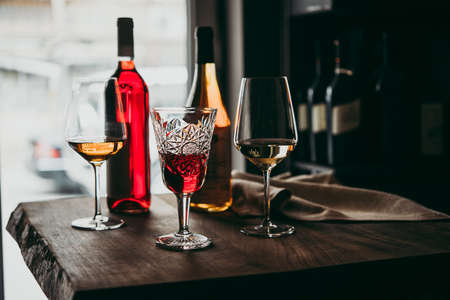 Photo for Different glasses and bottles of wine served on a wooden table in a bar or a wine shop. - Royalty Free Image