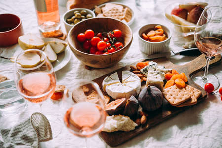Photo for A dinner table served with different kinds of cheese,fruits and rose wine. - Royalty Free Image