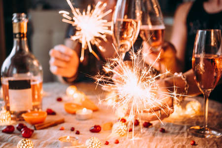 Photo pour Friends celebrating Christmas or New Year eve party with Bengal lights and rose champagne. - image libre de droit