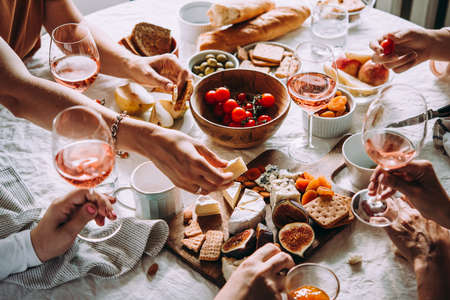 Photo for Friends having a dinner party with different kinds of appetizers and rose wine. - Royalty Free Image