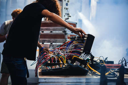 Photo pour Musician performs on stage using modular synthesizers. Electronic music and professional music equipment concept. - image libre de droit