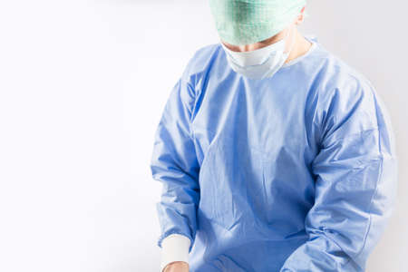 Foto de Surgeon doctor in sterile gloves preparing for operation in hospital. He is wearing surgical cap and blue gown - Imagen libre de derechos