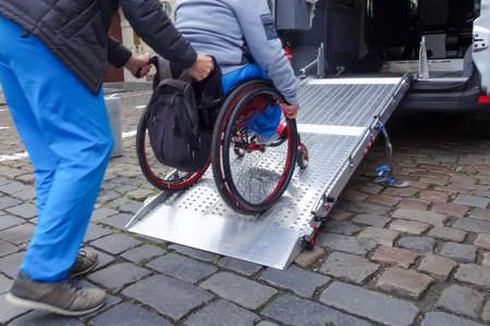 Photo pour Assistant helping disabled person on wheelchair with transport using accessible van ramp - image libre de droit