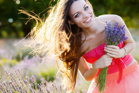Photo for Beautiful long-haired brunette in a lavender field - Royalty Free Image