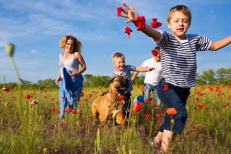 Family of four person playing on the poppy field