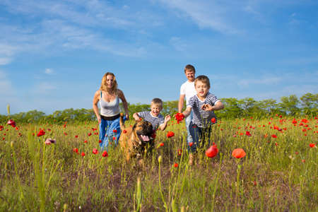 Photo for Family of four person and dog playing on the poppy field - Royalty Free Image