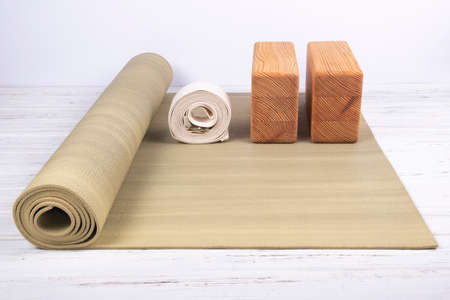 Photo pour Green yoga mat, two wooden blocks and white belt on white wooden background with copy space. Yoga practice, relaxation and meditation concept - image libre de droit