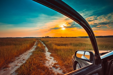 Foto de Dirty rural road in autumn fall field, meadow, countryside. View from car window. Freedom and dream concept - Imagen libre de derechos