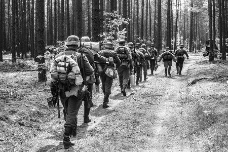 Foto de Unidentified Re-enactors Dressed As World War II German Soldiers Walks On Forest Road. Black And White Photography - Imagen libre de derechos