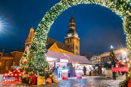 Foto de Riga, Latvia. Christmas Market On Dome Square With Riga Dome Cathedral. Christmas Tree And Trading Houses. Famous Landmark At Winter Xmas Evening Night In Illuminations Light. - Imagen libre de derechos
