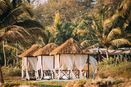 Foto de Goa, India. Gazebo Tents With Strawing Roof For Tourists On Beach With Tables And Sunbeds Inside. - Imagen libre de derechos