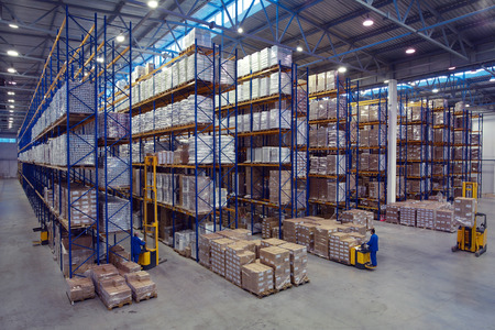 Foto de St. Petersburg, Russia - November 21, 2008: Forklift palletiser carrying palletising on the territory of the warehouse with pallet storage rack system. The interior of a large goods warehouse with shelves of pallet rack system storage. - Imagen libre de derechos