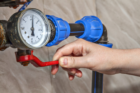 Photo for Water gauge pressure, hand shut off main valve, close-up. - Royalty Free Image