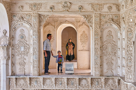 Kashan, Iran - April 26, 2017: muslim man with his son stand near the altar in Tabatabaei historical house, behind a woman in hijab stands.