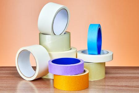 Photo pour Duct tape in assortment lies on table against background of orange wall. - image libre de droit