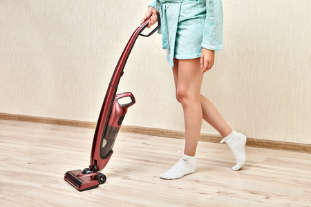 Photo pour Handheld upright burgundy vacuum cleaner, with help of which the cleaning woman is  vacuuming in an empty room. - image libre de droit