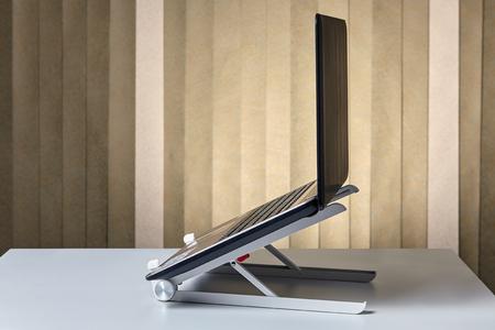 Foto de Cooling stand dock desk holder for notebook with open laptop, side view. - Imagen libre de derechos