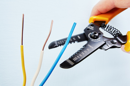 Foto de Electrician uses the wire stripper cutter to remove of insulation from the tip of each of the wires during electrical wiring services, close-up. - Imagen libre de derechos