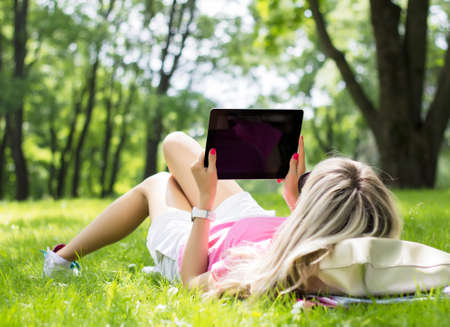 Foto de Relaxed young woman using tablet computer outdoors - Imagen libre de derechos