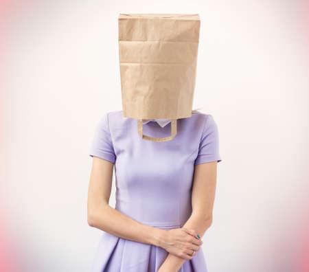 Photo pour Young woman with paper bag over her head   - image libre de droit