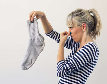 Photo pour Woman holding dirty socks with her nose closed   - image libre de droit