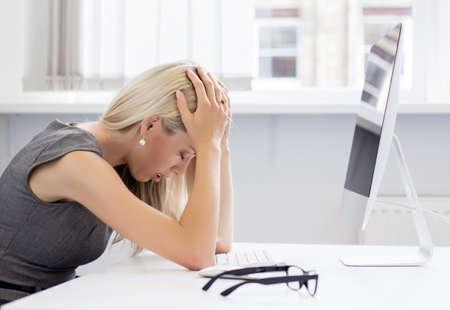 Foto de Overworked and frustrated young woman in front of computer   - Imagen libre de derechos