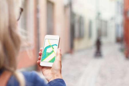 Photo pour Tourist using navigation app on the mobile phone.   - image libre de droit