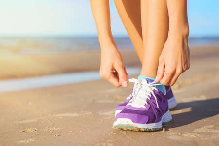 Foto de Woman wearing running shoes on the beach - Imagen libre de derechos