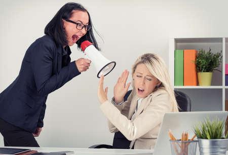 Foto de Mad boss shouting at employee on megaphone - Imagen libre de derechos