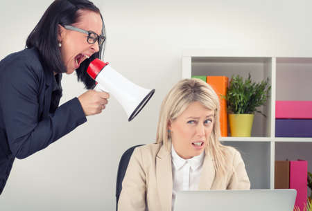 Foto de Angry boss shouting at employee on megaphone - Imagen libre de derechos