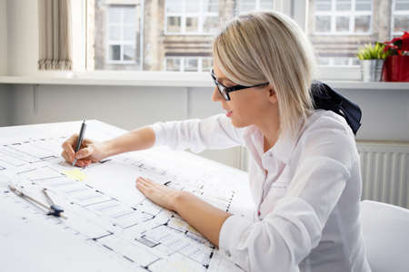 Foto de Young female architect working on blueprint - Imagen libre de derechos