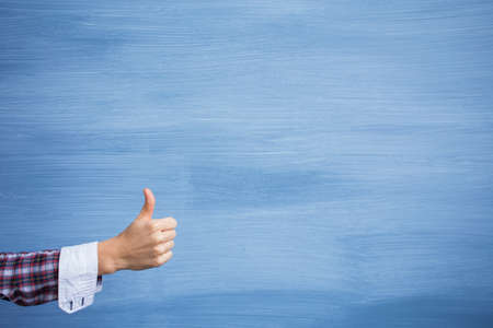 Foto de Hand showing thumbs up gesture on blue background - Imagen libre de derechos