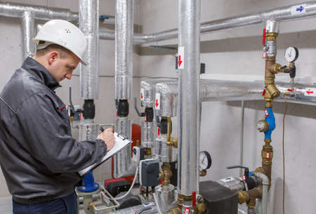 Photo pour Technician inspecting heating system in boiler room - image libre de droit