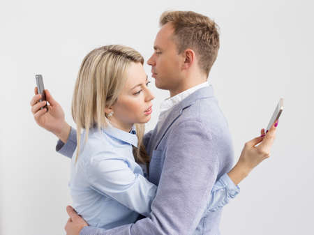 Photo pour Young couple embracing and still using their mobile phones - image libre de droit
