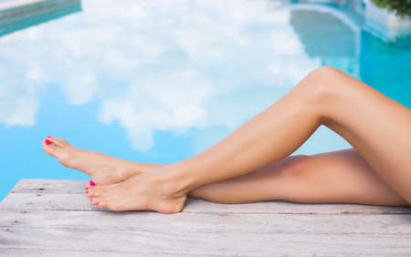 Photo pour Beautiful slim women legs by the swimming pool - image libre de droit