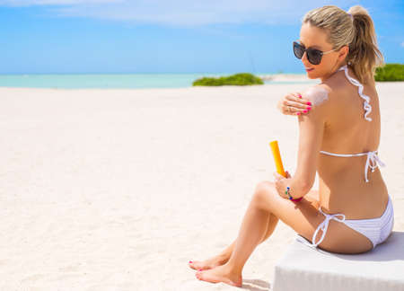 Photo pour Woman sunbathing on the beach and applying sun protection cream - image libre de droit