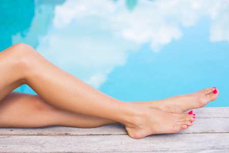 Foto de Beautiful women legs by the swimming pool - Imagen libre de derechos