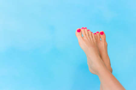 Photo for Bare woman feet over blue swimming pool water - Royalty Free Image