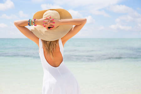 Photo pour Young woman in white dress and straw hat on the beach - image libre de droit