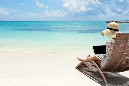 Foto per Business woman using laptop computer on the beach - Immagine Royalty Free