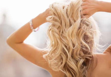Photo pour Blonde woman holding her hands in hair - image libre de droit