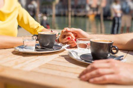 Foto de Couple holding hands and drinking coffee in cafe outdoors - Imagen libre de derechos