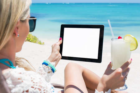 Relaxed woman drinking cocktail and holding tablet computer on the beach