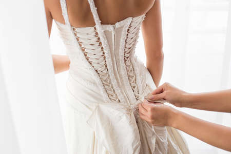 Photo pour Helping bride with a dress - image libre de droit