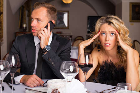 Photo for Woman at dinner date being annoyed of man talking on the phone - Royalty Free Image