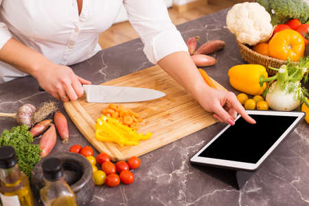 Photo for Woman following the recipe in tablet - Royalty Free Image