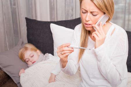 Foto de Mother calling doctor and looking at thermometer - Imagen libre de derechos