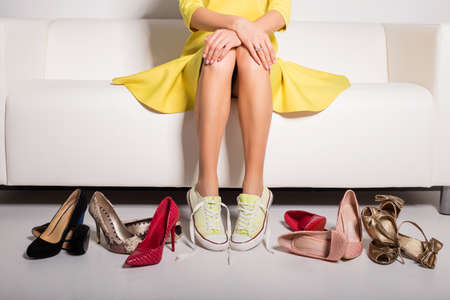 Photo pour Woman sitting on couch and trying on shoes - image libre de droit