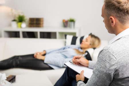 Photo pour Woman lying on couch at doctors office - image libre de droit